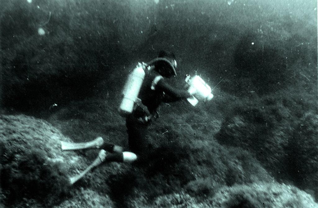 Аквалангисткинобоксом на фоне камней